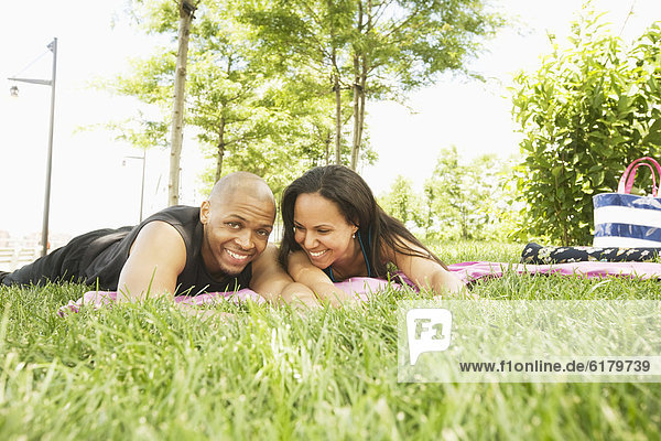 Smiling couple laying in grass at park