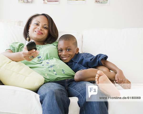Black mother and son watching TV on living room sofa