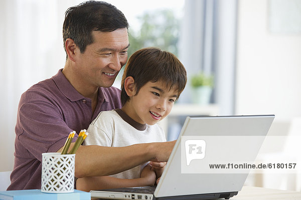 Smiling father and son using laptop