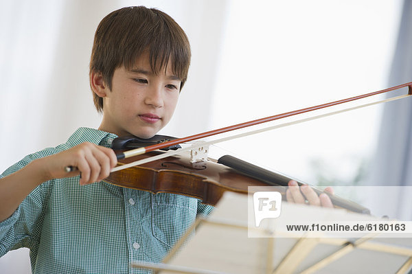 Mixed race boy playing violin