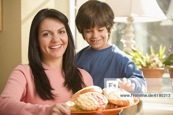 Sohn  Hispanier  halten  Teller  Keks  Mutter - Mensch