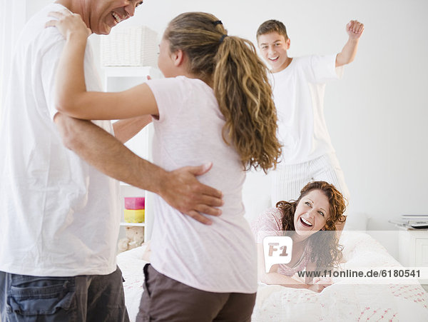 Laughing Hispanic family playing together