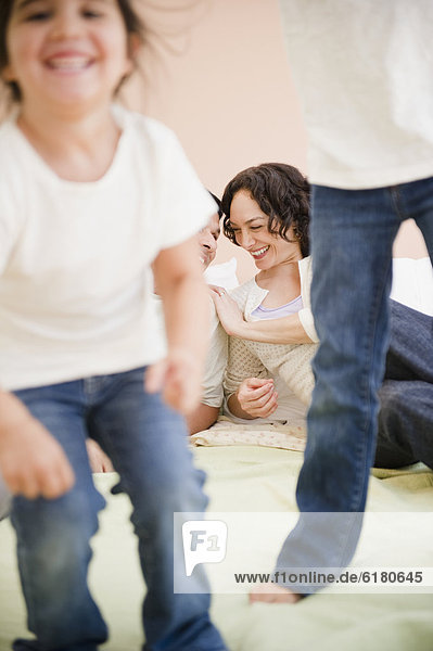 sehen  Menschliche Eltern  Bett  springen  Tochter