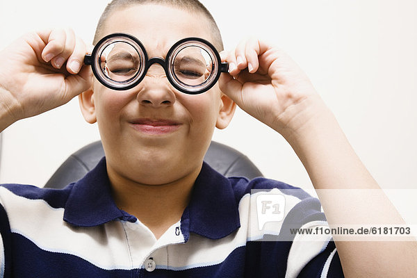Asian boy taking off eye glasses
