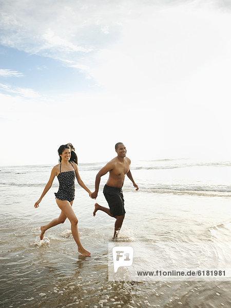 Fröhliches Paar rennt Hand in Hand am Strand