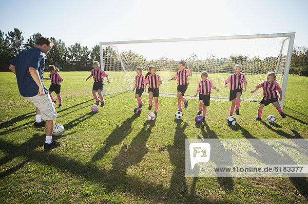Fußballspieler üben Mädchen