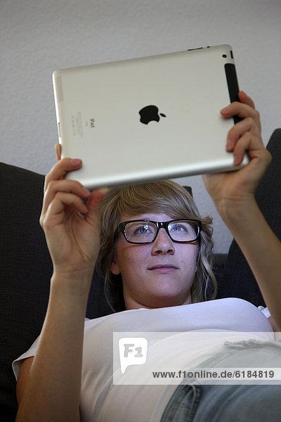 Junge Frau liegt auf einem Sofa und surft mit einem iPad  Tablet-Computer drahtlos im Internet
