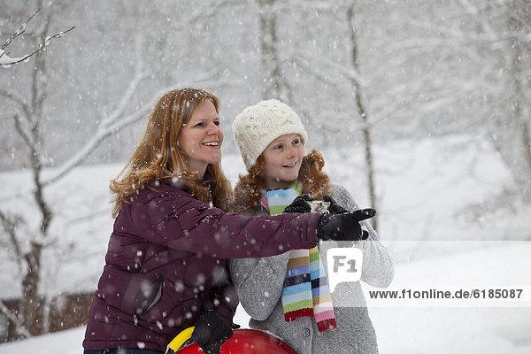 stehend  Europäer  Tochter  Mutter - Mensch  Schlitten  Schnee