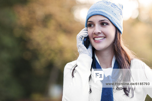 Mixed race woman in cap talking on cell phone