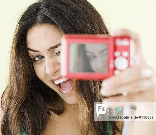 Middle Eastern woman taking self-portrait