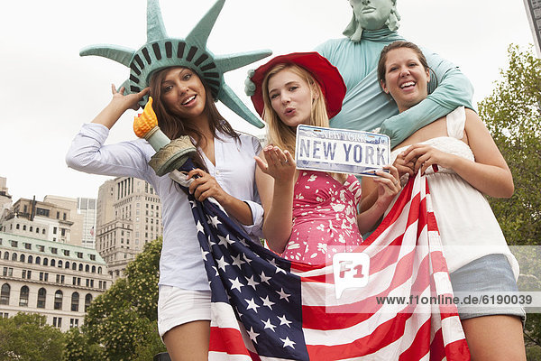 Laughing friends visiting the Statue of Liberty