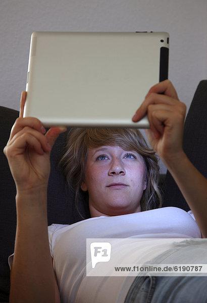 Junge Frau liegt auf Sofa und surft drahtlos im Internet mit einem iPad Tablet-Computer