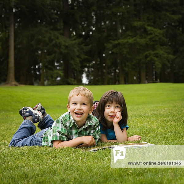 Brother and sister reading story book in park