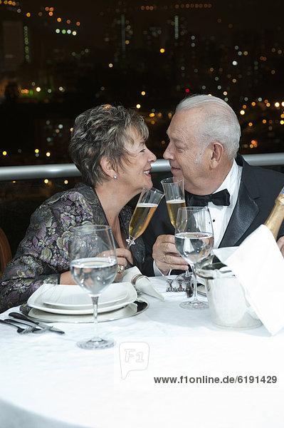 Senior  Senioren  Hispanier  Restaurant  zuprosten  anstoßen  Champagner