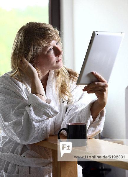 Junge Frau im Bademantel morgens mit einer Tasse Kaffee in der Küche  liest mit einem iPad  Tablet-Computer in einer Online-Zeitung
