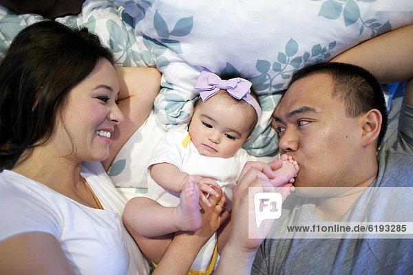 liegend  liegen  liegt  liegendes  liegender  liegende  daliegen  Menschlicher Vater  Bett  Mädchen  Mutter - Mensch  Baby
