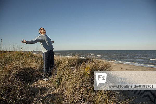 nahe  stehend  Mann  Ozean  Sand  Arme ausbreiten  Arme ausstrecken  Düne  strecken