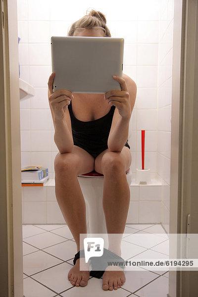 Junge Frau auf der Toilette surft mit einem iPad  Tablet-Computer per Drahtlosverbindung im Internet