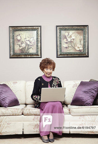 Senior Caucasian woman using laptop on sofa