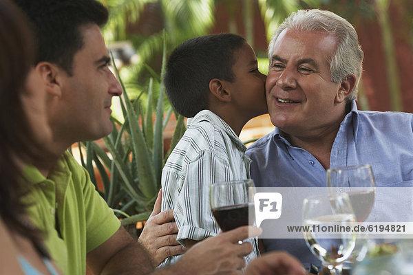 Hispanic boy kissing grandfather