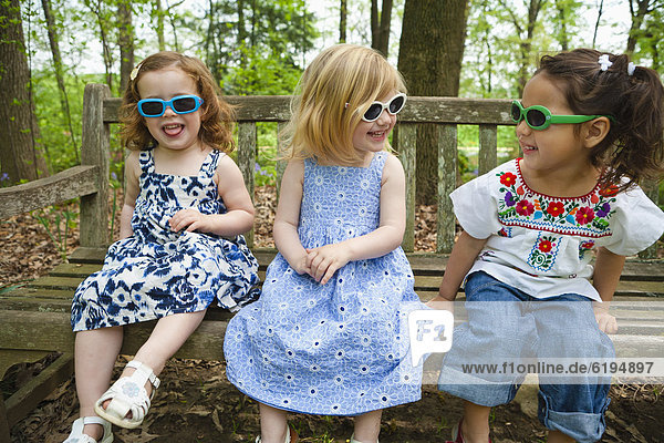 Girls in sunglasses sitting on bench together
