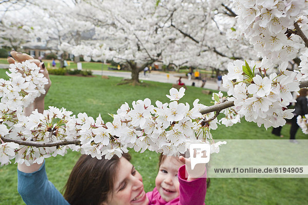 Caucasian mother and daughter looking at spring flowers