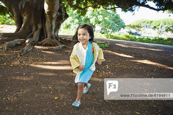 Smiling girl running outdoors