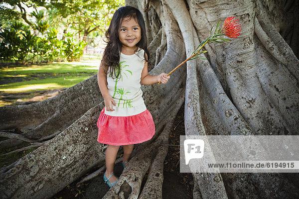 Smiling girl holding exotic flower