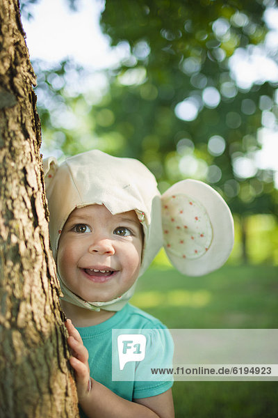 Caucasian girl in mouse costume standing near tree