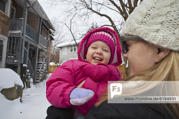 Mother holding grinning girl in coat
