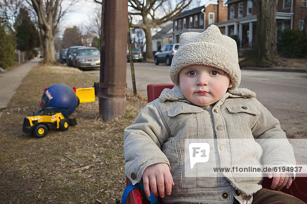 Boy in coat and cap sitting in yard