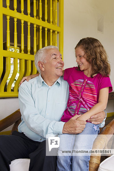 Grandfather sitting with granddaughter