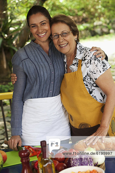Hispanic mother and daughter cooking together