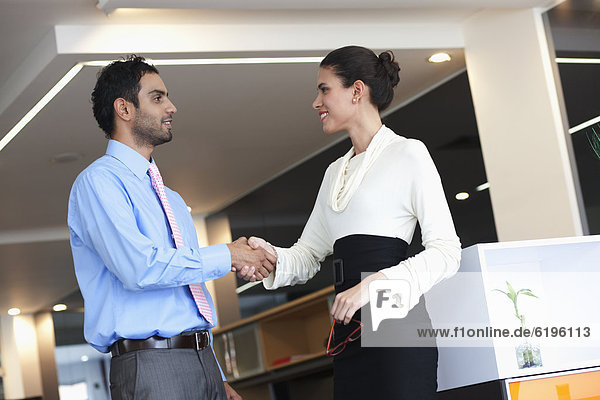 Smiling Hispanic business people shaking hands in office