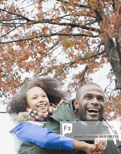 African father carrying daughter piggyback
