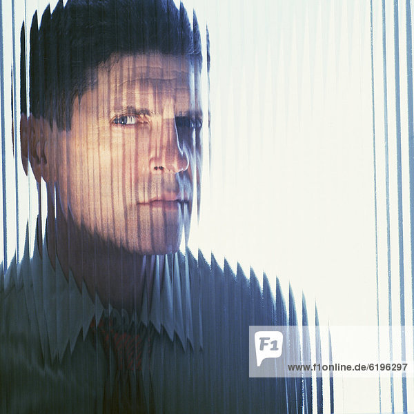 Suspicious businessman looking through glass wall