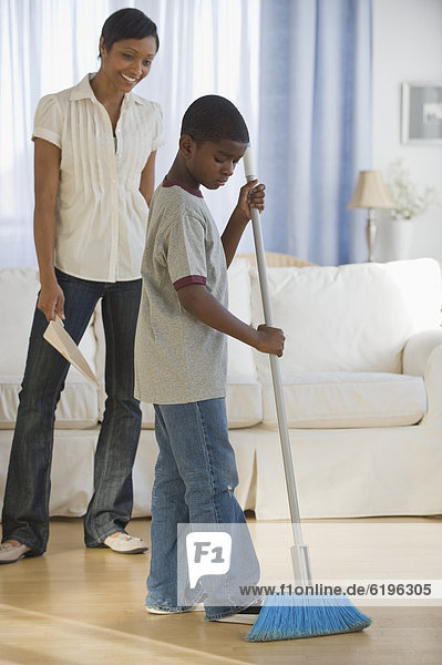 African mother and son doing housework together