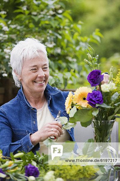 Senior  Senioren  Frau  Blume  lächeln  arrangieren  Blumenvase