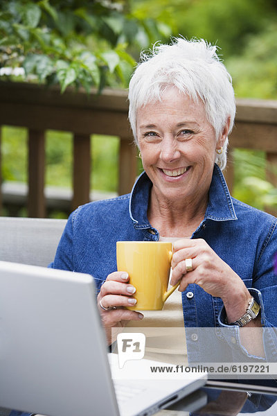 Außenaufnahme Senior Senioren Frau Notebook Kaffee freie Natur