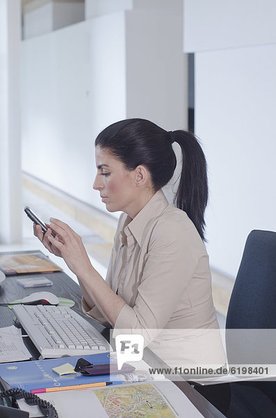 Hispanic businesswoman text messaging at desk