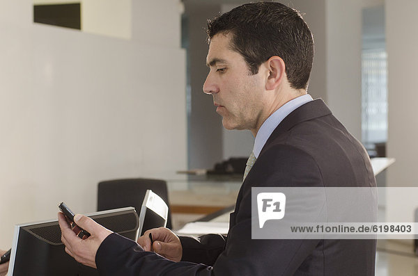 Handy  Geschäftsmann  Hispanier  Text  Büro  Kurznachricht
