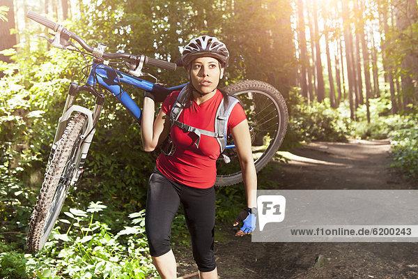 Hispanic woman carrying mountain bike in forest