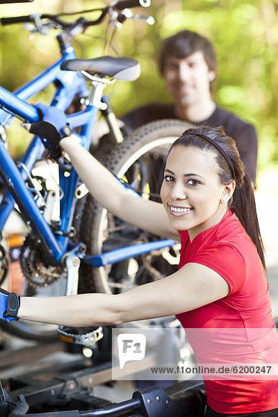 Couple loading mountain bikes on rack