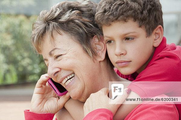 Handy  sprechen  umarmen  Junge - Person  Hispanier  Großmutter