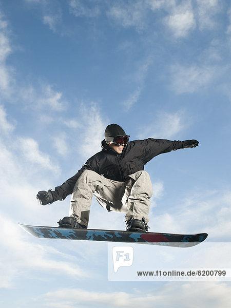 Europäer  Mann  Snowboard  In der Luft schwebend