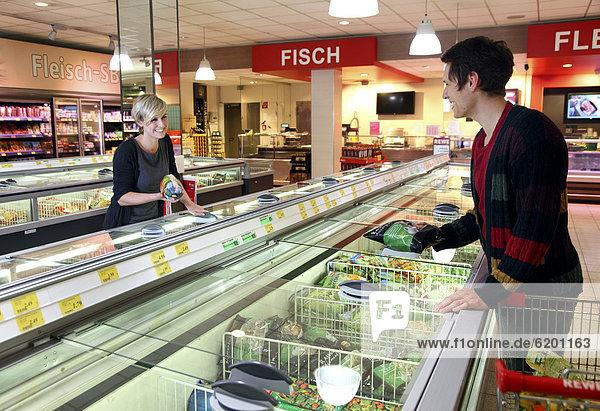 Kunden an Tiefkühltruhen  Tiefkühlprodukte  Lebensmittelabteilung  Supermarkt  Deutschland  Europa