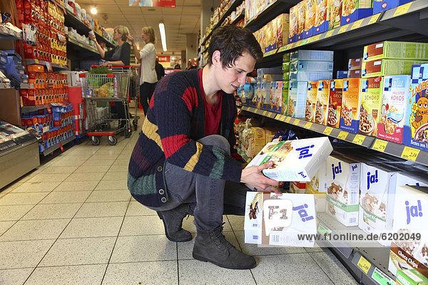 Mann kauft Mueslimischung der JA-Marke ein  Lebensmittelabteilung  Supermarkt  Deutschland  Europa