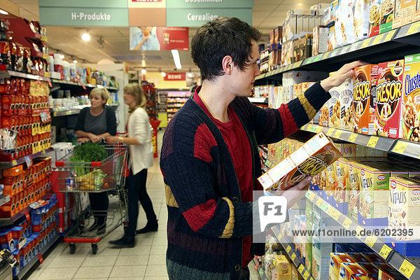 Mann kauft Mueslimischung ein  Lebensmittelabteilung  Supermarkt  Deutschland  Europa