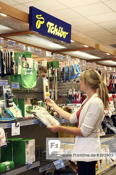 Kundin sieht sich Produkte aus dem Tchibo-Warenangebot an  Lebensmittelabteilung  Supermarkt  Deutschland  Europa