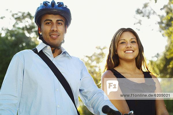 Hispanic man wearing bike helmet posing with girlfriend